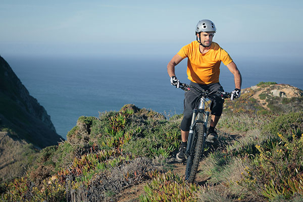 mountain-biker-riding-dirt-trail-PY7SA7Y