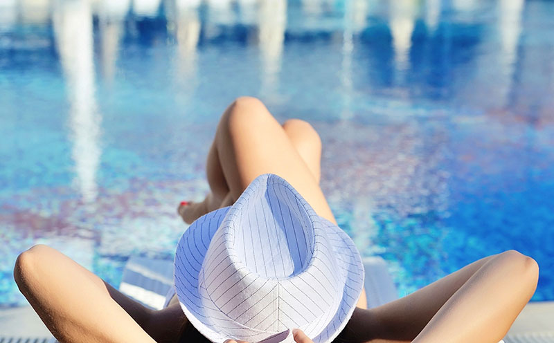 woman-in-white-hat-lying-on-a-lounger-near-the-swi-P9ZLEE2